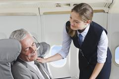 Germany, Bavaria, Munich, Young stewardess taking care of senior businessman in - stock photo