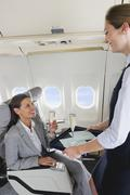 Germany, Bavaria, Munich, Stewardess serving champagne to businesswoman in - stock photo