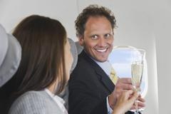 Germany, Bavaria, Munich, Businessman and woman toasting champagne in business - stock photo