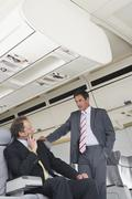 Germany, Bavaria, Munich, Businessmen talking in business class airplane cabin - stock photo