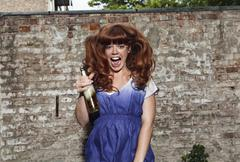 Saksa, Berlin, Nuori nainen hyppää lähellä seinää, nauraa, muotokuva Kuvituskuvat