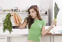 Germany, Berlin, Young woman holding carrots and leek in domestic kitchen - stock photo