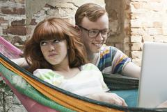 Germany, Berlin, Young woman using laptop in hammock with young man beside her Stock Photos