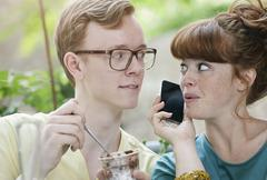 Germany, Berlin, Close up of young couple listening to cell phone and whispering - stock photo