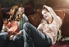 Germany, Berlin, Young women holding champagne glass and resting on couch, Stock Photos