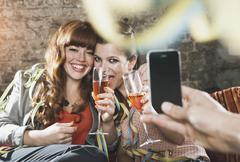 Germany, Berlin, Young women holding champagne glass and man taking photo with - stock photo