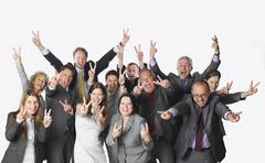 Large group of business people with victory sign against white background - stock photo