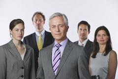 Business people against white background, smiling, portrait Stock Photos