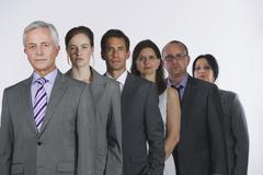Business people standing in row against white background Stock Photos