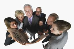 Business people reading newspaper against white background Stock Photos