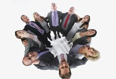 Business people forming huddle and looking up against white background Stock Photos