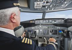 Germany, Bavaria, Munich, Senior flight captain piloting aeroplane from airplane - stock photo