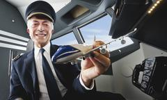 Germany, Bavaria, Munich, Senior flight captain holding model aeroplane in Stock Photos
