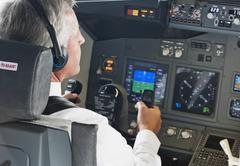 Germany, Bavaria, Munich, Senior flight captain wearing headphone and piloting - stock photo