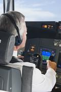 Germany, Bavaria, Munich, Senior flight captain wearing headphone and piloting - stock photo