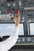 Germany, Bavaria, Munich, Senior flight captain's hand piloting aeroplane from Stock Photos