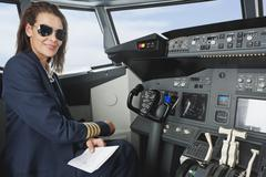 Germany, Bavaria, Munich, Woman flight captain with map in airplane cockpit - stock photo