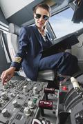 Germany, Bavaria, Munich, Woman flight captain piloting aeroplane from airplane - stock photo