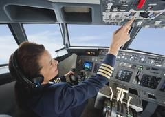 Stock Photo of Germany, Bavaria, Munich, Woman flight captain piloting aeroplane from airplane