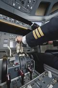 Stock Photo of Germany, Bavaria, Munich, Hands of pilot piloting aeroplane from airplane