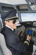 Germany, Bavaria, Munich, Pilot piloting aeroplane from airplane cockpit - stock photo
