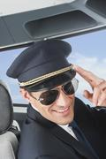 Germany, Bavaria, Munich, Pilot wearing aviator glasses and saluting in airplane Stock Photos