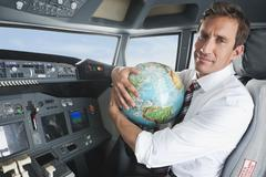 Germany, Bavaria, Munich, Businessman with world globe in airplane cockpit - stock photo