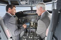 Germany, Bavaria, Munich, Businessmen showing digital table in airplane cockpit - stock photo