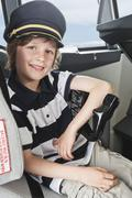 Germany, Bavaria, Munich, Boy wearing captain's hat and playing in airplane - stock photo