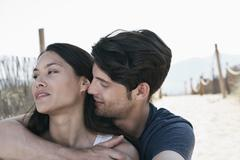 Stock Photo of Spain, Majorca, Young man embracing woman on boardwalk at beach
