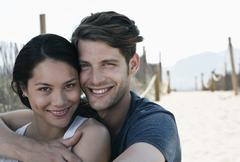 Stock Photo of Spain, Majorca, Young man embracing woman on boardwalk at beach, portrait