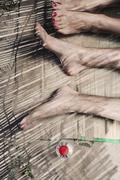 Stock Photo of Spain, Majorca, Young couple's feet lying on straw mat at beach