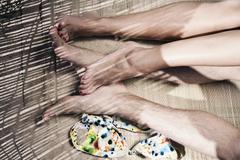 Spain, Majorca, Young couple's feet lying on straw mat at beach Stock Photos