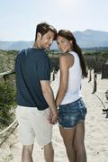 Spain, Majorca, Young couple holding hands and walking on boardwalk at beach - stock photo