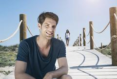 Stock Photo of Spain, Majorca, Young man sitting on boardwalk and woman walking in background