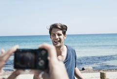 Spain, Majorca, Young woman taking picture of man at beach - stock photo