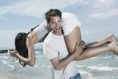 Stock Photo of Spain, Majorca, Young man carrying woman on shoulders at beach