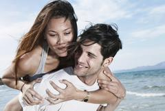 Spain, Majorca, Young man carrying woman on back at beach - stock photo