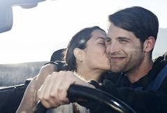 Spain, Majorca, Young woman kissing man in cabriolet car, close up - stock photo