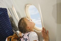Germany, Munich, Bavaria, Girl looking through window in economy class airliner Stock Photos