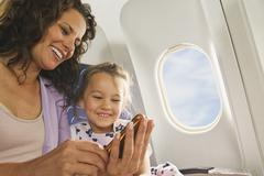 Germany, Munich, Bavaria, Woman and girl with cell phone in economy class - stock photo