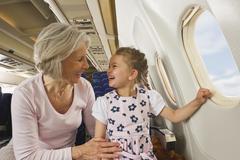 Germany, Munich, Bavaria, Senior woman and girl smiling beside window in economy - stock photo