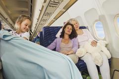 Germany, Munich, Bavaria, Women sleeping and girl pulling blanket in economy - stock photo