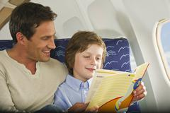 Germany, Munich, Bavaria, Man and boy reading book in economy class airliner Stock Photos