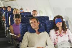 Germany, Munich, Bavaria, Passengers sleeping in economy class airliner Stock Photos