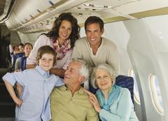 Germany, Munich, Bavaria, Group of passengers in economy class airliner, smiling Stock Photos
