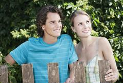 Young couple standing behind wood fencing, smiling - stock photo