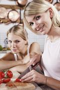 Stock Photo of Two young women cutting tomatoes in kitchen, smiling