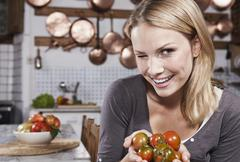 Young woman winking and holding tomatoes in kitchen, smiling, portrait - stock photo