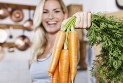 Young woman holding carrots in kitchen, smiling, portrait - stock photo